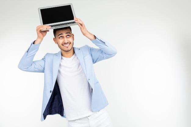 Sorrir jovem morena alegremente mantém um laptop com espaço em branco para inserir uma página de site em um fundo branco com espaço de cópia