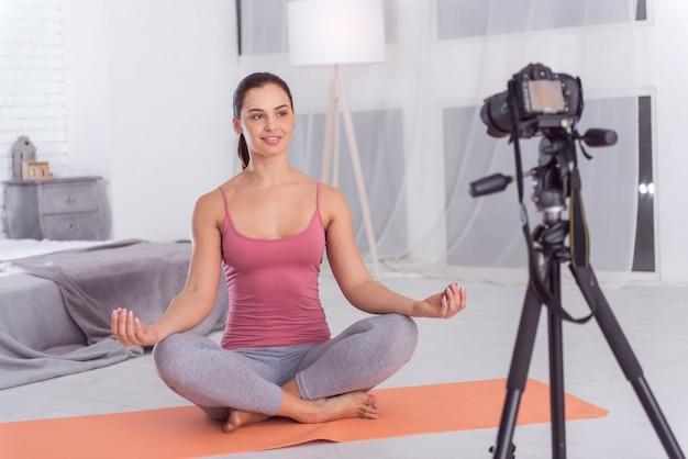 Sorrir. linda exuberante blogueira atlética de cabelos escuros sorrindo e fazendo ioga no tapete enquanto faz um vídeo para seu blog