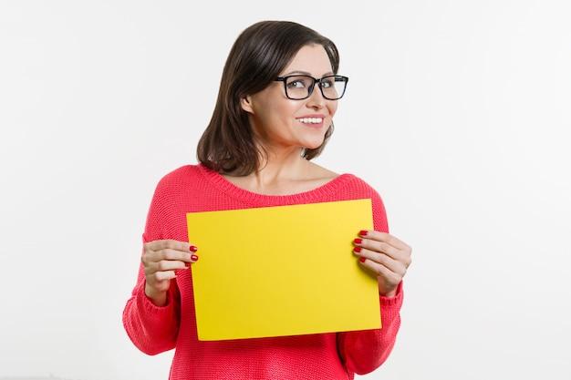 Sorrir meio envelhecido mulher com folha de papel amarela