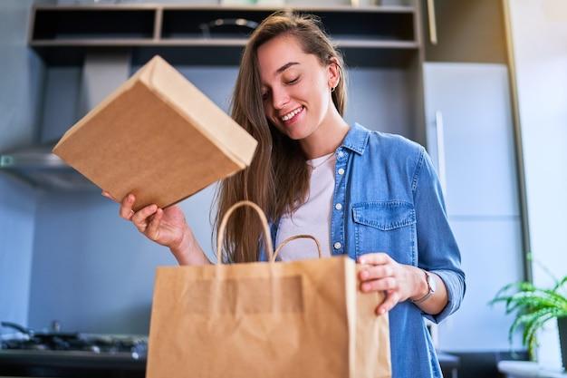 Sorrir satisfeito feliz adulto casual alegre jovem milenar garota cliente recebeu sacos de papelão com comida e bebidas para viagem em casa. conceito de serviço de entrega rápida