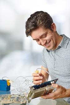 Sorrir tecnologia masculina limpa processador de computador com defeito