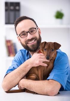 Sorrir veterinário masculino está segurando um cachorro.