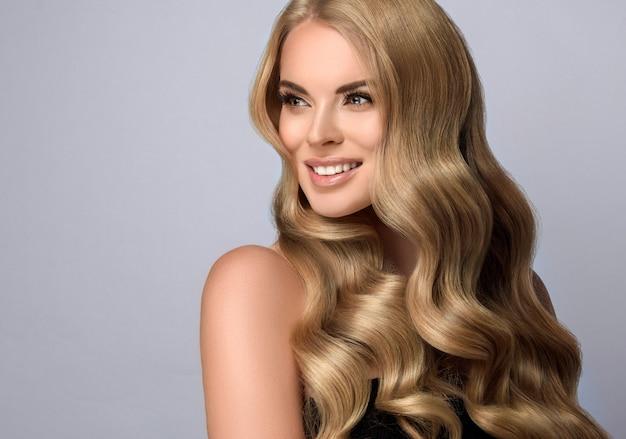 Sorriso aberto no rosto de uma mulher de cabelos loiros com cachos volumosos, nos cabelos longos. modelo com cabelos longos, densos e crespos e maquiagem delicada. arte para pentear, cuidados com os cabelos e produtos de beleza.
