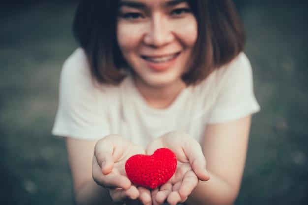 Sorriso adolescente menina com coração vermelho na mão para dar o conceito de saúde médica de doação de ajuda.