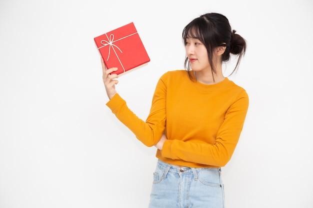 Sorriso asiático bonito feliz da mulher com caixa de presente vermelha
