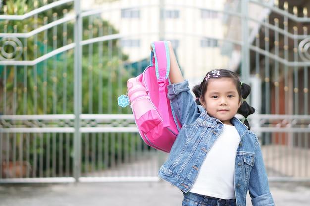 Sorriso asiático da menina e estudante que guardam e mostram a mochila cor-de-rosa