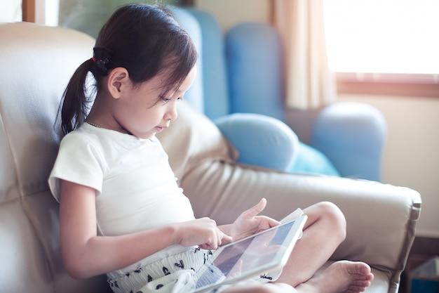 Sorriso asiático da menina que senta-se no sofá usando a almofada digital da tabuleta na sala de visitas em casa.