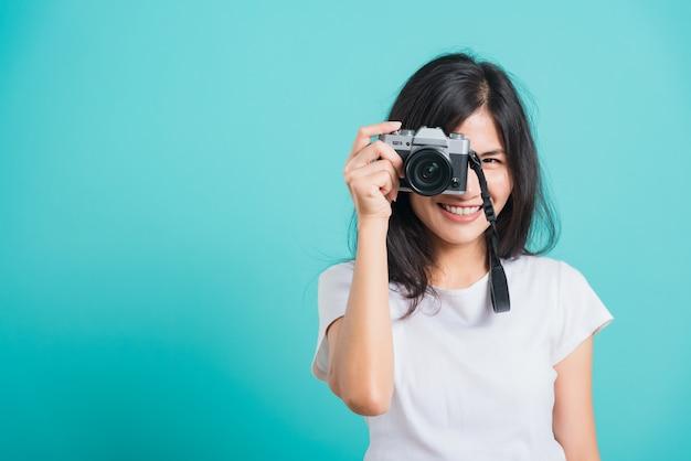 Sorriso asiático da mulher que está com a câmera fotográfica mirrorless