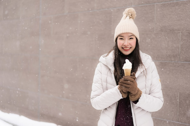 Sorriso asiático novo bonito da mulher e feliz com gelado na estação do inverno da neve