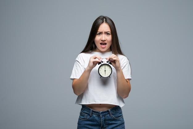 Sorriso asiático novo da mulher com um relógio isolado no fundo cinzento