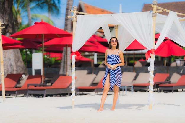 Sorriso asiático novo do retrato feliz em torno do oceano do mar da praia com a palmeira de coco para férias do feriado