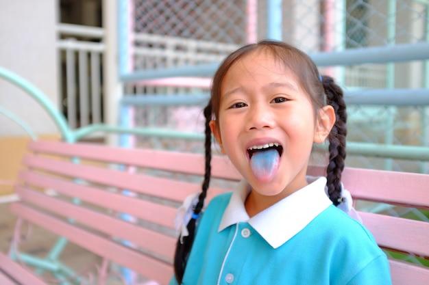 Sorriso asiático pequeno insolente da menina da criança da cara insolente e picar para fora a língua colorida azul.