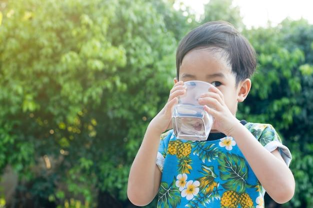 Sorriso bonito asiático menino água potável para saudável e refrescante com fundo verde árvore