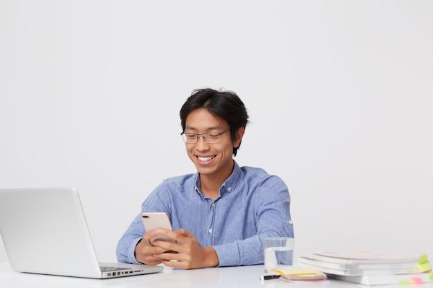 Sorriso bonito jovem empresário asiático de óculos e camisa azul usando telefone celular e laptop sentado à mesa sobre a parede branca
