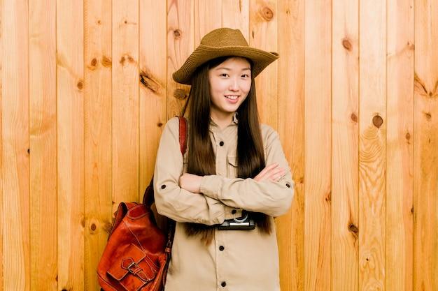Sorriso chinês novo da mulher do viajante seguro com braços cruzados.