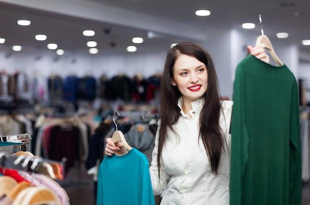 Sorriso comprador feminino com suéteres