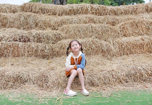 Sorriso da menina da criança pequena e da roupa morna que sentam-se na pilha da palha em uma estação do inverno.