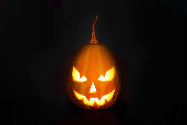 Sorriso de abóbora de halloween e olhos scrary para noite de festa. close-up vista da assustadora abóbora de halloween em fundo preto.