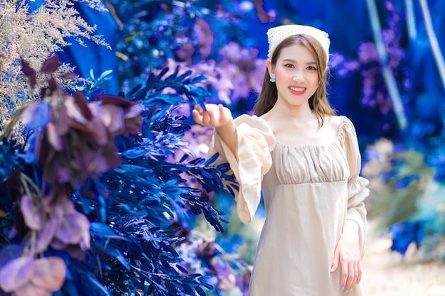 Sorriso de carrinho de menina linda asiática admira com flores no jardim azul e floresta como pano de fundo.