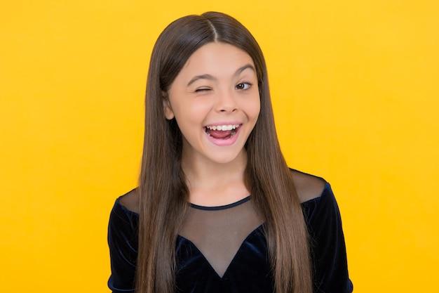 Sorriso de criança menina feliz piscando com a boca aberta e mostrando fundo amarelo de dentes saudáveis, odontologia.