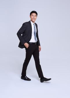 Sorriso de empresário asiático de rosto bonito e amigável no terno formal em um estúdio de fundo branco, tiro.