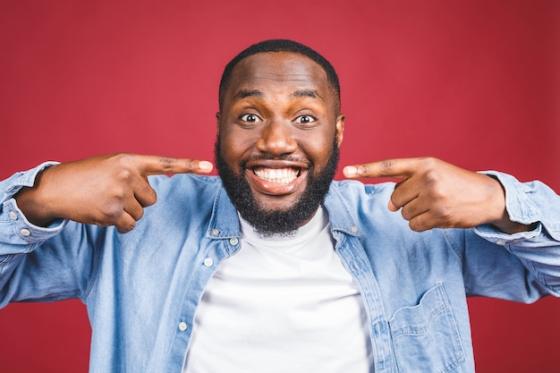 Sorriso de homem afro-americano. cuidados de saúde dentários isolados sobre fundo vermelho.