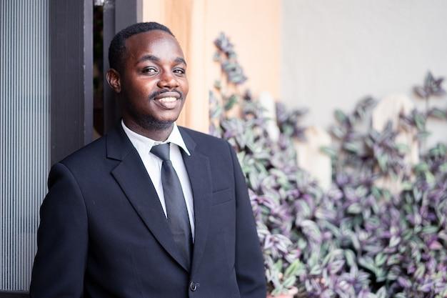 Sorriso de homem de negócios africano e bem chegar ao restaurante