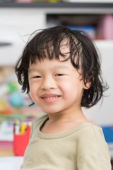 Sorriso de menino asiático tailandês com camisa verde em desfocar o fundo
