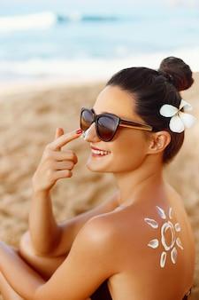 Sorriso de mulher aplicar protetor solar no rosto
