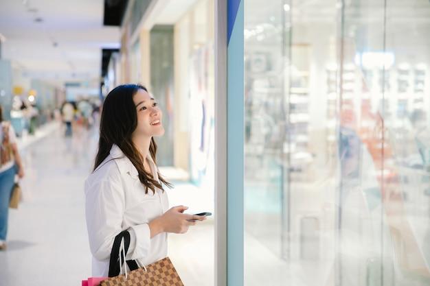 Sorriso de mulher asiática com sacos de compras desfrutar em shopping center