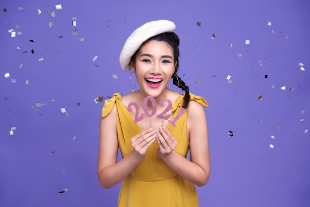 Sorriso de mulher bonita asiática dando boas-vindas ao ano novo 2021 com festa de confetes de prata na parede roxa brilhante.