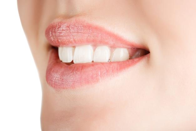 Sorriso de mulher bonita e saudável, close-up isolado no fundo branco
