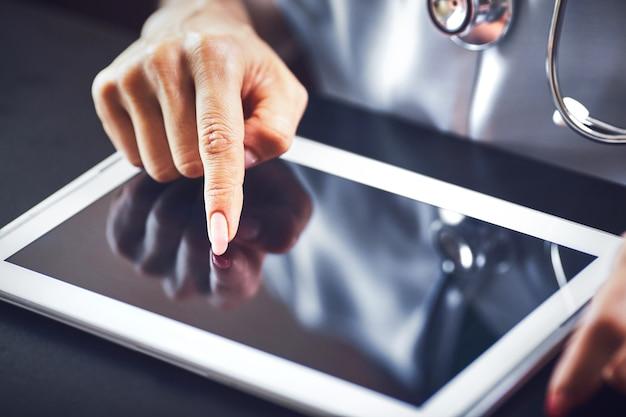 Sorriso de mulher médico segurar o tablet pc, usando o computador.