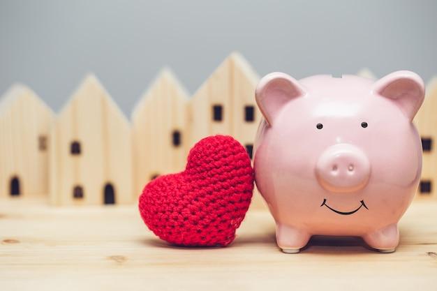 Sorriso de porco bonito com coração vermelho no fundo da vila natal para o conceito de casa segura de comunidade de amor.