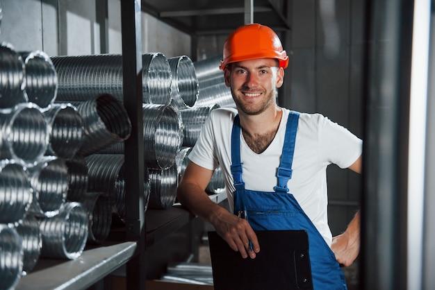Sorriso dentuço. homem de uniforme trabalha na produção. tecnologia industrial moderna.