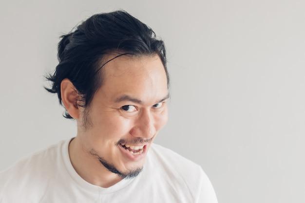 Sorriso engraçado sorriso rosto de homem em t-shirt branca e parede cinza.