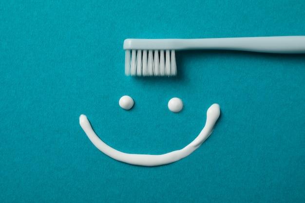 Sorriso feito de creme dental na superfície turquesa