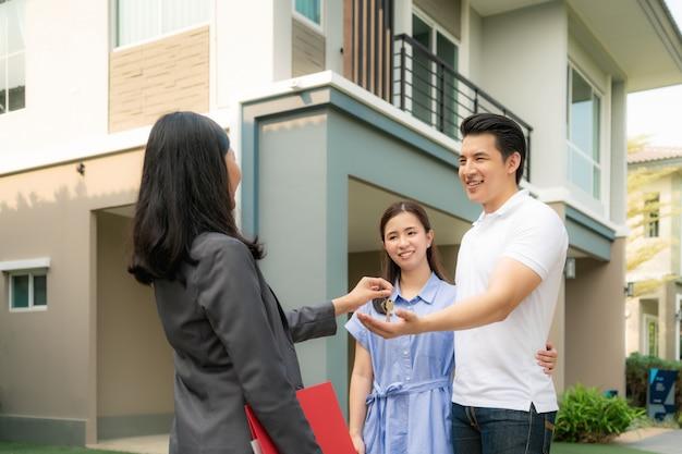 Sorriso feliz asiático jovem casal leva chaves nova casa grande de agente imobiliário ou corretor de imóveis em frente a sua casa depois de assinar o contrato