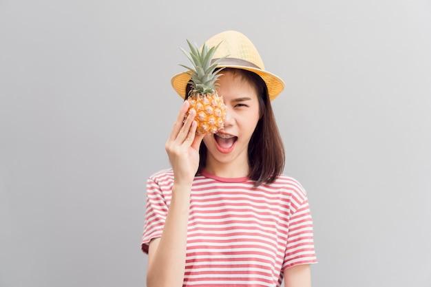 Sorriso feliz da moça e alegre no vestido vermelho, guardando o abacaxi na mão.