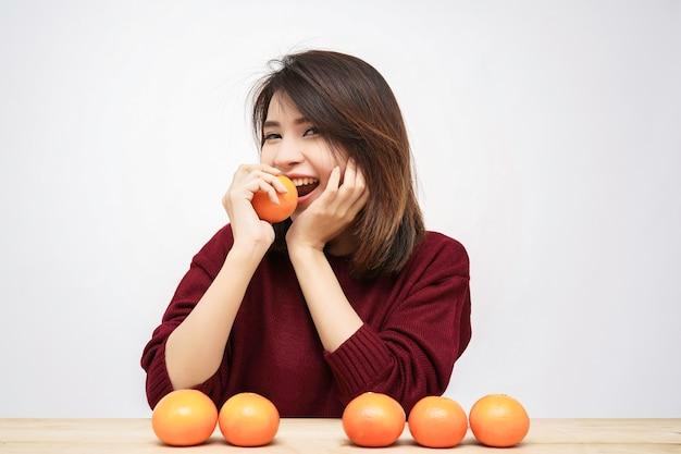 Sorriso feliz da mulher bonita nova asiática com fundo alaranjado do branco da fruta.