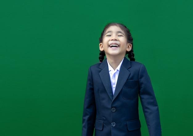 Sorriso feliz de crianças em idade escolar asiática com uniforme formal de negócios sobre fundo verde.