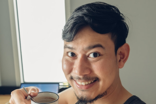 Sorriso feliz homem selfie-se com uma xícara de café em um dia quente e aconchegante.