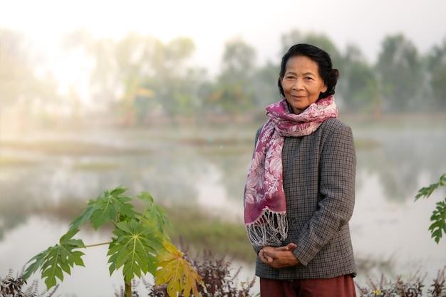 Sorriso feliz idoso idoso asiático com a fazenda natural em segundo plano, conceito de estilo de vida de mulheres idosas asiáticas