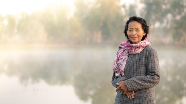 Sorriso feliz idoso idoso asiático com o lago natural ao fundo, conceito de estilo de vida de mulheres idosas asiáticas