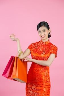 Sorriso feliz linda mulher asiática e compras no ano novo chinês no fundo rosa.
