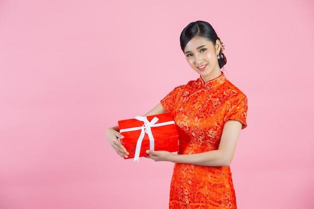 Sorriso feliz linda mulher asiática e segurando a caixa de presente no ano novo chinês em fundo rosa.