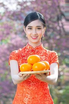 Sorriso feliz linda mulher asiática e segurando laranjas frescas no ano novo chinês em fundo rosa.