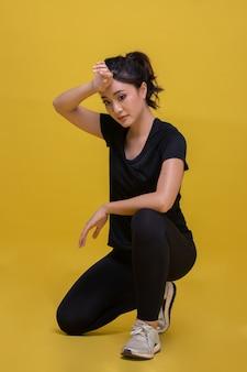 Sorriso feliz. mulher bonita asiática jovem fitness esporte está descansando de suor cansado e exercícios de alongamento