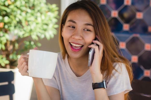 Sorriso feliz mulheres de negócios asiáticos usando celular falando no café e segurando uma xícara de café