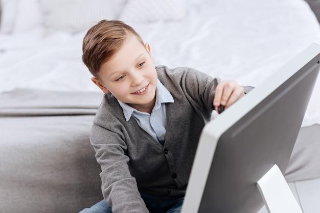 Sorriso feliz. positivo bom rapaz encantado sorrindo e olhando para a tela digital enquanto está de bom humor
